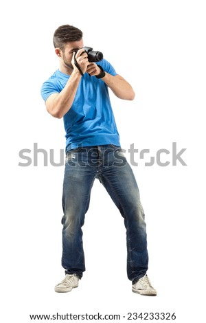 Standing young man taking photo with dslr. Full body length portrait isolated over white background.