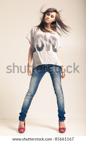 Standing young woman wearing jeans and t-shirt with an inscription love - stock photo