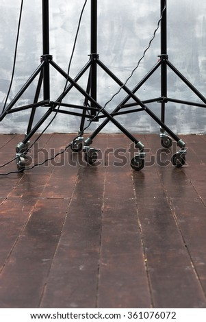 Stands for lighting equipment on the wooden floor
