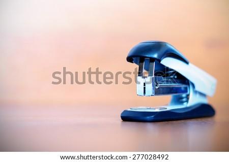 stapler on wooden background  - stock photo