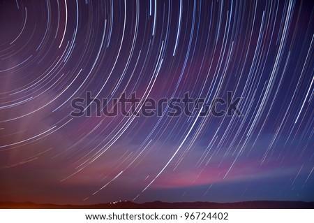 Star and auto trails with a Quadrantid Meteor above Mt. Hamilton in San Jose, California. - stock photo