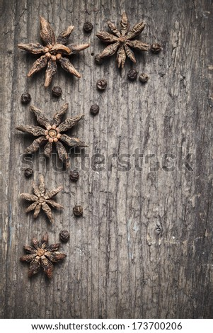 star anise and black peppercorns on aged wood