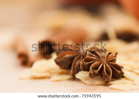 Star anise and peeled almonds with cinnamon in the back. - stock photo
