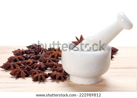 Star Anise in white granite mortar and pestle on wooden background - stock photo