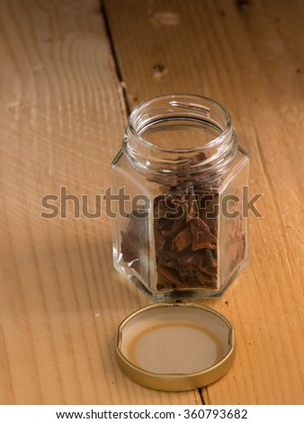 Star Anise inside a container with wooden background
