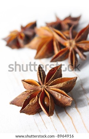 Star anise on weathered white timber.  Focus on front star.  Delicious liquorice smell and flavour.