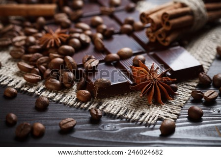 Star anise with cinnamon and coffee beans near chocolate bar, rustic wooden background - stock photo