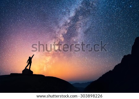 Star-catcher. A person is standing next to the Milky Way galaxy pointing on a bright star. - stock photo