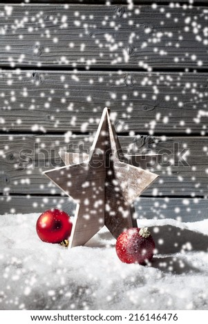 Star decoration red christmas spheres on pile of snow against wooden wall - stock photo
