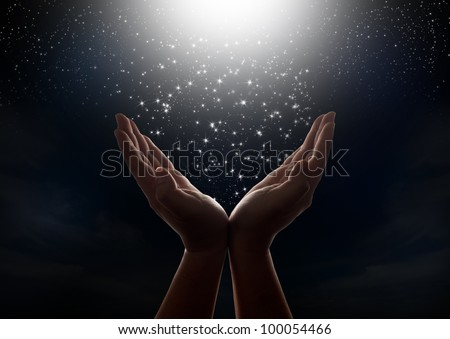 Star falling from the dark night sky to hands - stock photo