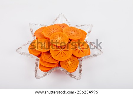 Star platter with sliced persimmons - angled view on white background - stock photo
