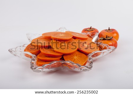 Star platter with sliced persimmons - side view - stock photo