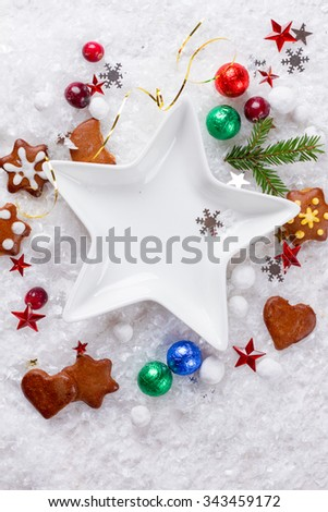 Star shape plate with gingerbread cookies and candy in Christmas setting, selective focus - stock photo