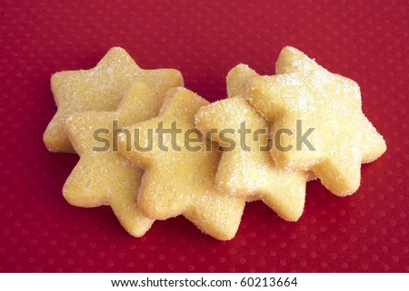 Star shaped butter biscuits on a red background for a Christmas theme - stock photo