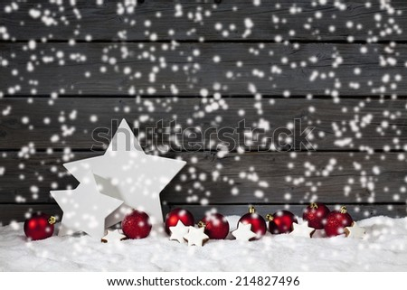 Star shaped christmas decoration christmas bulbs cinnamon stars on pile of snow against wooden wall snow is falling - stock photo