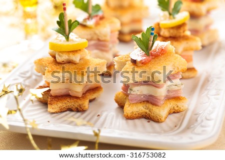 Star shaped toasts with smoked salmon, ham and cheese. - stock photo