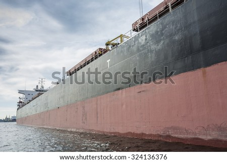 Starboard-side of a huge bulk carrier. Blue clouds at the background of the ship.  - stock photo
