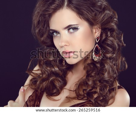 Stare. Long eyelashes makeup. Wavy hair. Attractive girl with fashion Earring. Expressive eyes. Elegant lady over studio dark background.