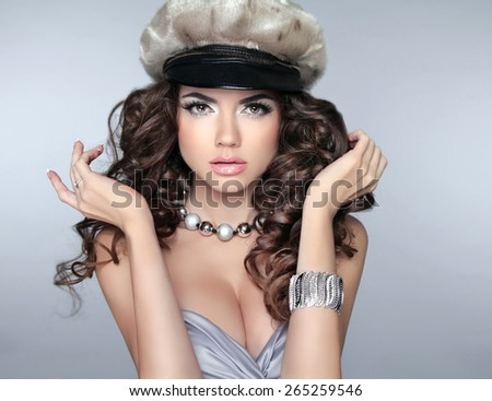 Stare. Makeup. Beautiful brunette girl model with long curled hair and fashion jewelry isolated on studio grey background. Lady wearing in fur cap.
