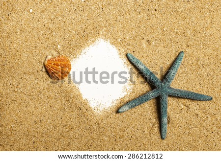Starfish and sheet of paper with sand as background with copy space. - stock photo