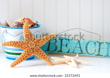 Starfish and wooden beach sign with pail of seashells - stock photo