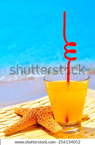 Starfish, glass of orange cocktail against the blue sea - stock photo