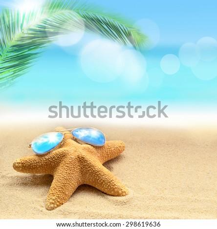 Starfish in sunglasses on the summer beach - stock photo