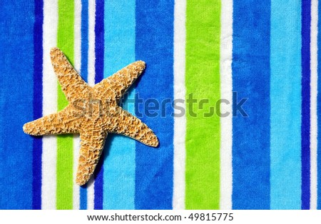 Starfish laying on striped towel room for your text - stock photo