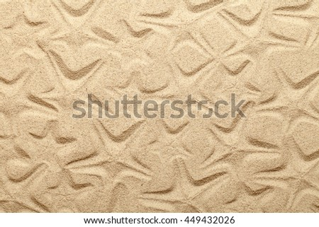 Starfish patterns on sandy beach background