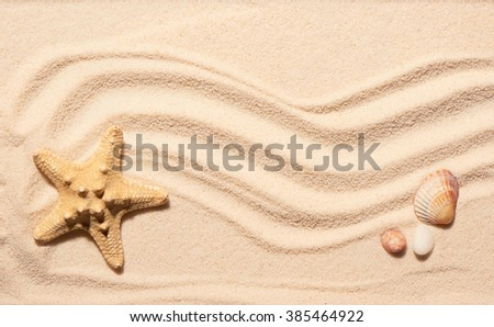 Starfish, scallop seashell and two stones on beach sand. Summer beach background. View from above