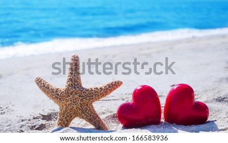 Starfish with two hearts  on the sandy beach by the ocean - stock photo