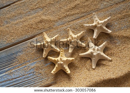 Starfishes on sand and planks - stock photo