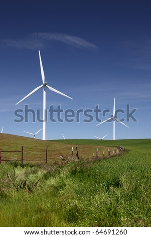Stark white power generating wind turbines behind green pasture left, wheatfields right, and blue skies.