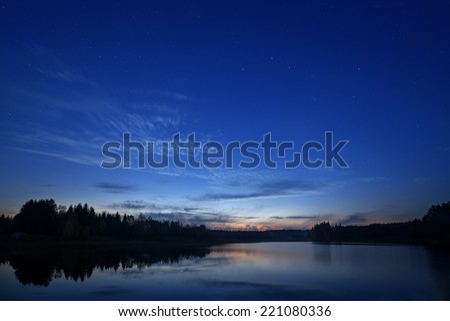 Starry night landscape near the lake - stock photo