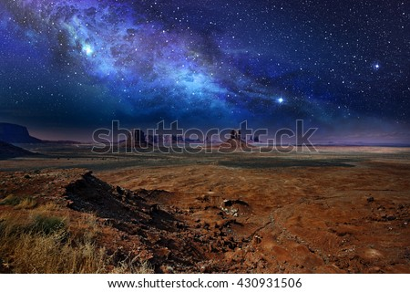 starry night sky over the monument valley - stock photo