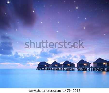 Starry skies over water villa cottages on island of Kuredu, Maldives, Lhaviyani atoll, shot with a tilt and shift lens - stock photo