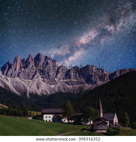 Starry sky above beautiful city in the mountains. - stock photo