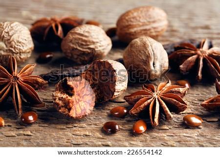 Stars anise with nutmeg on wooden background - stock photo