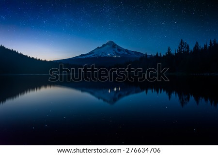Stars in the night sky and Mount Hood reflecting in Trillium Lake at night, in Mount Hood National Forest, Oregon. - stock photo