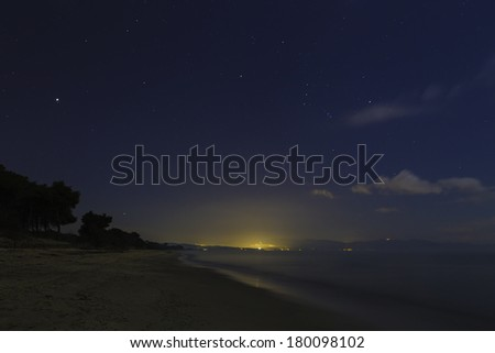 Stars shining over a mediterranean sandy beach with pine trees and the glow of a distant town / Distant town at night - stock photo