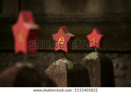 Stars with hammer and sickle at tombstones of cementery of russian soldiers fallen in second world war