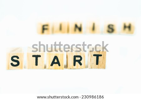 Start and finish, words made out of alphabet wood pieces on white background - stock photo