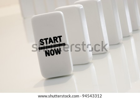 Start now message on aligned and standing dominoes - stock photo