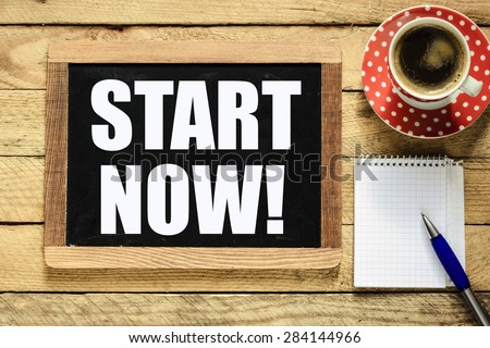 Start now on blackboard. Start now On blackboard with cup of coffee, notebook and pen on wooden background - stock photo