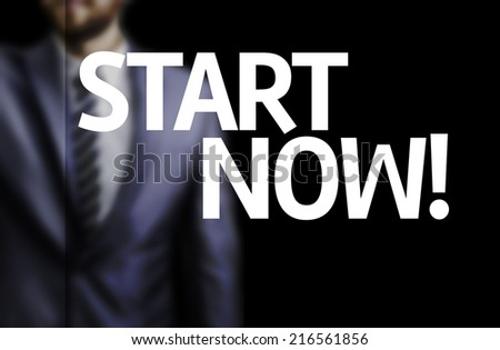 Start Now written on a board with a business man on background - stock photo