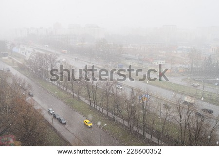 Start of the Russian winter in Russia. Snow falls in the city - stock photo
