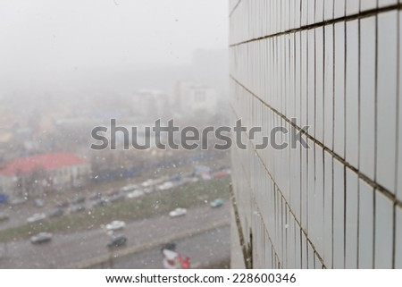 Start of the winter in Russia. Snow falls in the city (Near Wall) - stock photo