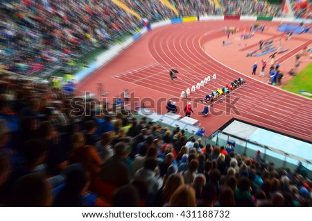 Start on 100m sprint. Professional athletes on stadium are on start blocks and the are ready to race. - stock photo