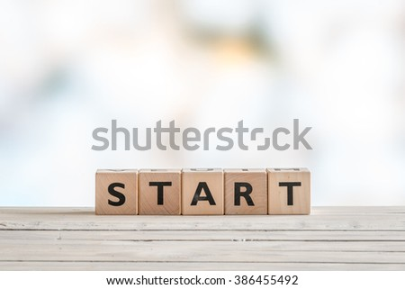 Start sign made with cubes on a wooden table - stock photo
