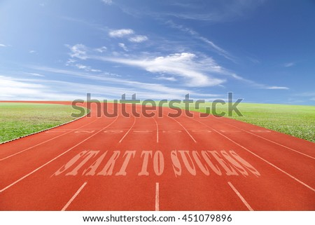 Start to Success written on running track written on Running track with green grass and blue sky white cloud background